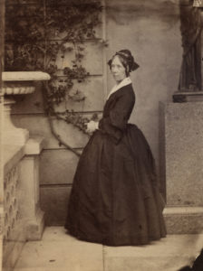 Marianne Skerret, black & white photograph taken around 1859. The photo shows a middle-aged woman in a dark dress with a hoopskirt.